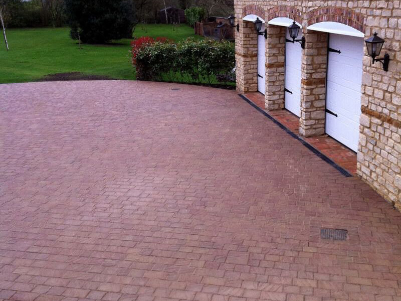 Block paving in front of stone garages
